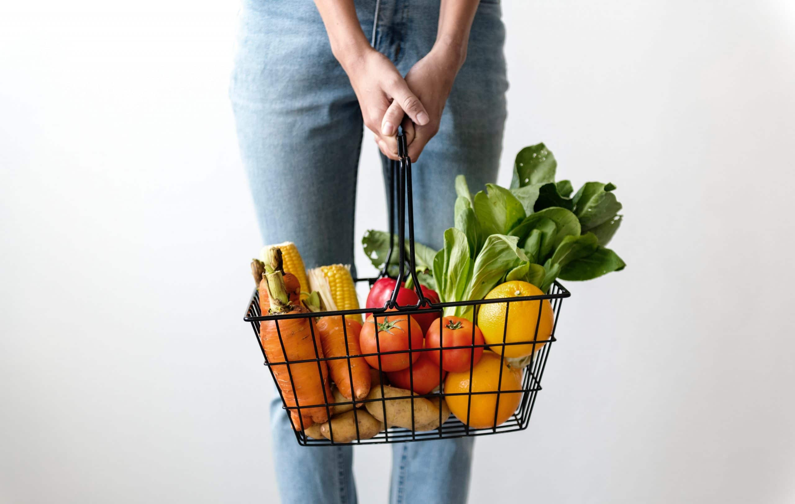 woman carrying a basket of fresh produce