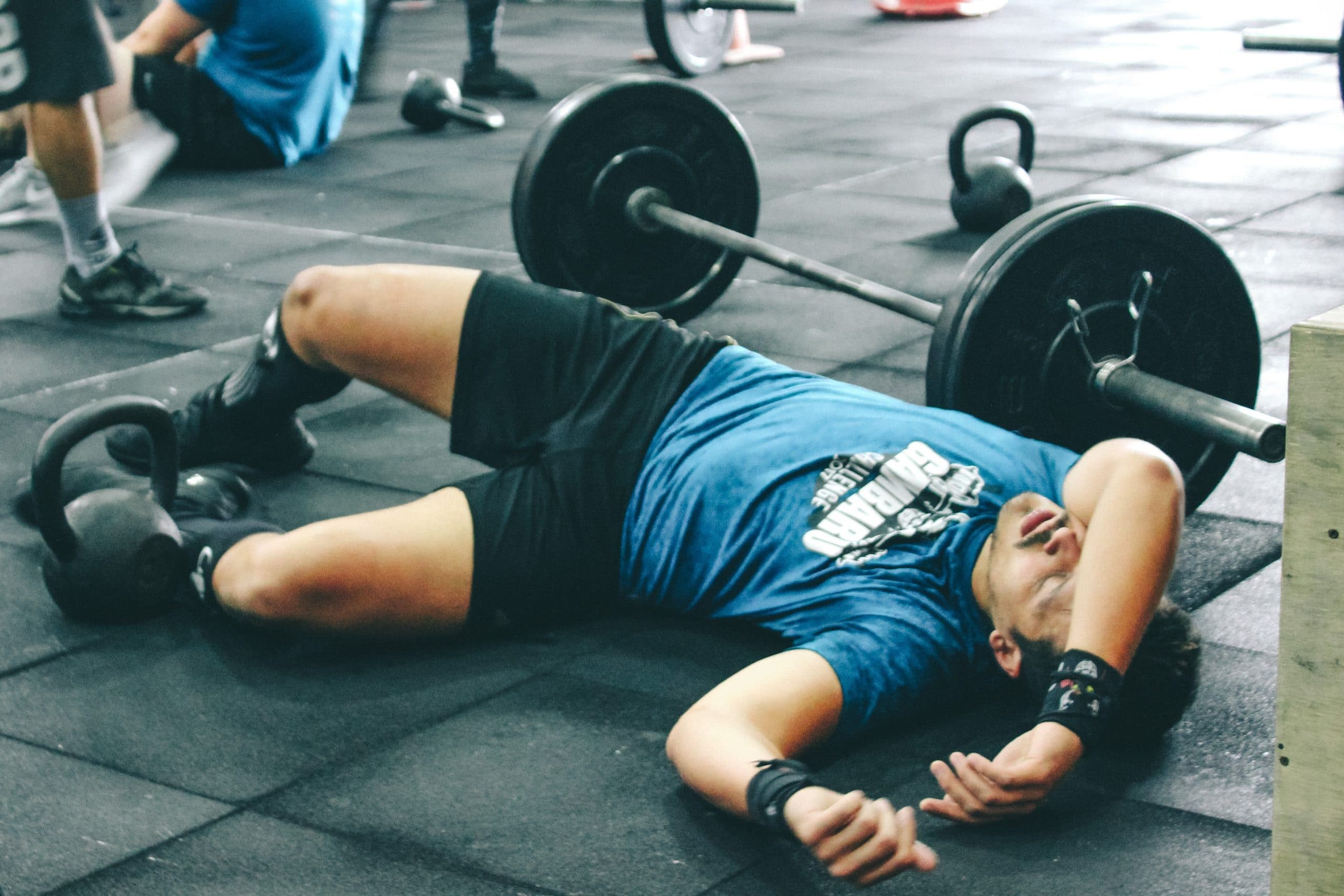 man laying on the floor looking tired after using barbell