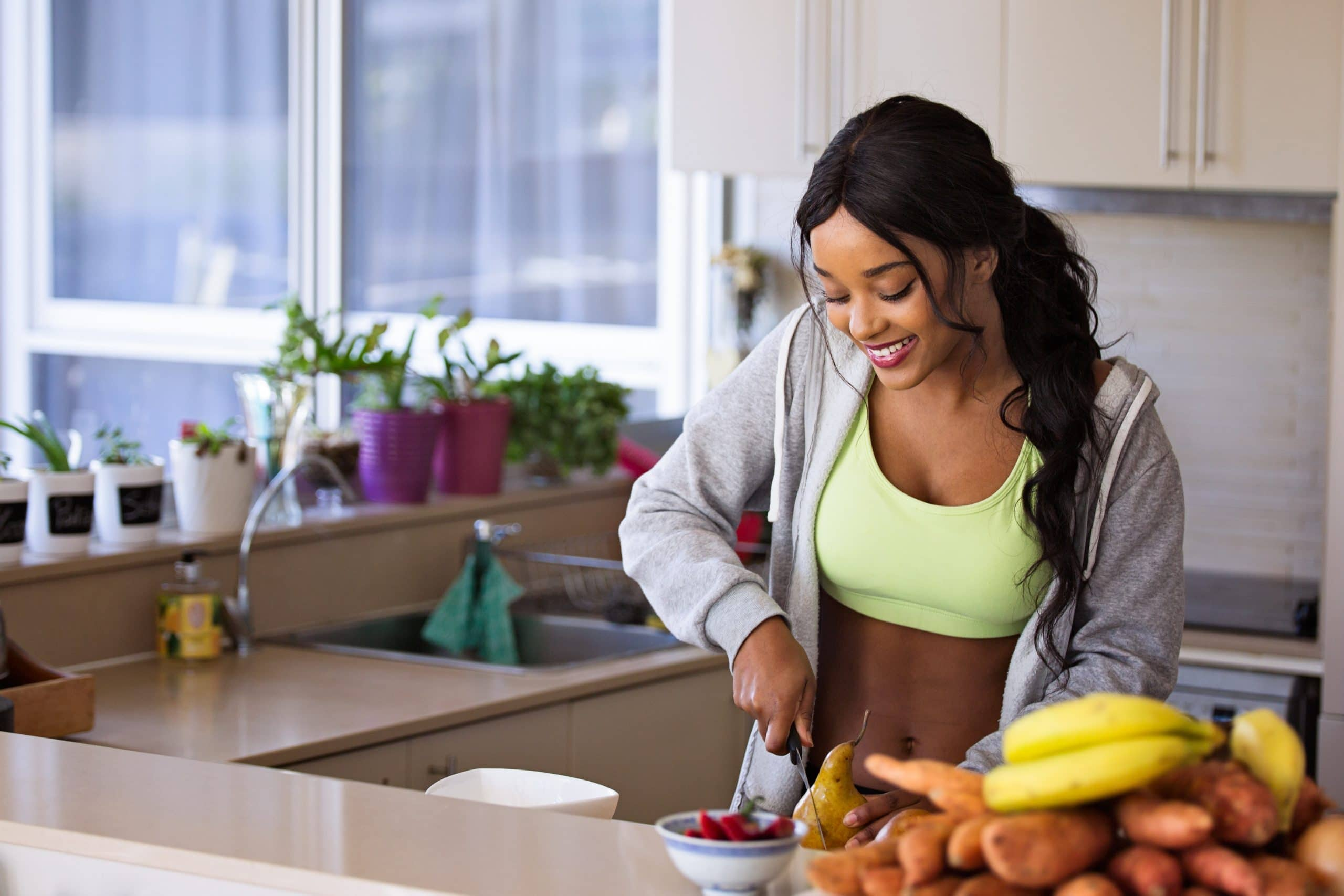 woman smiling while cutting fruit in kitchen