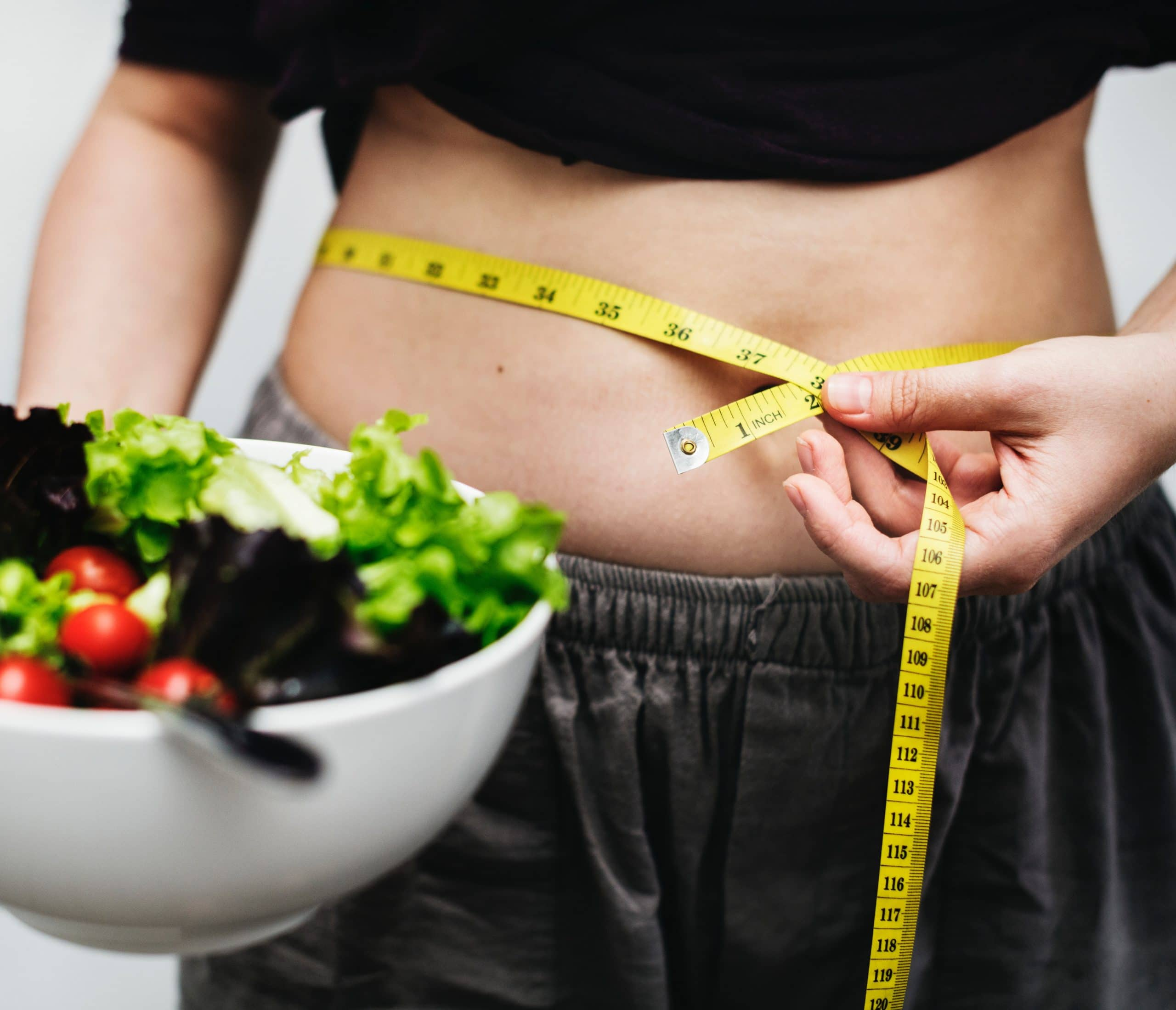 woman measuring her stomach with a bowl of salad in her hand