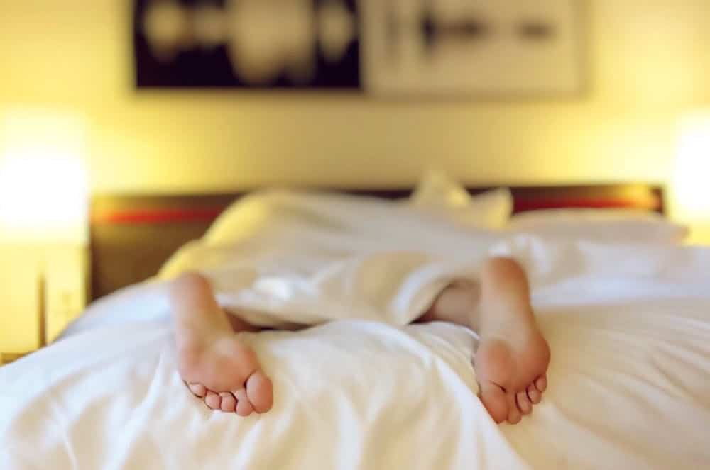 person sleeping on bed with feet outside the blanket