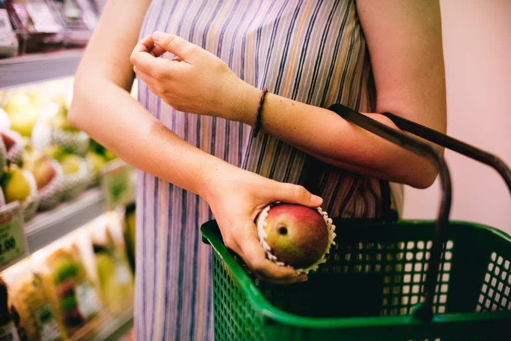 woman putting fruit into her shopping basket
