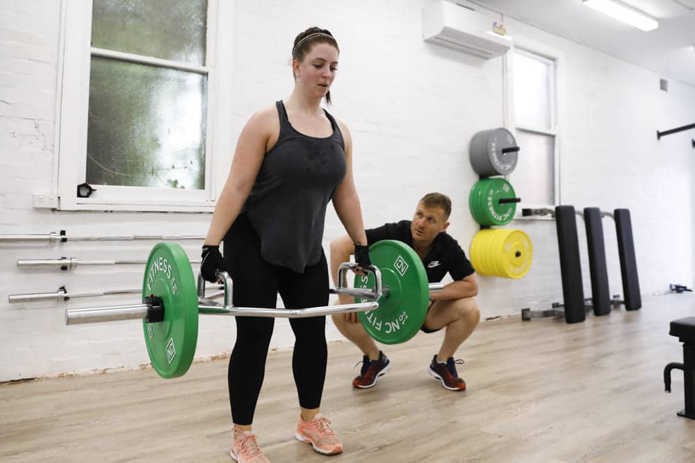 woman performing exercise with trainer