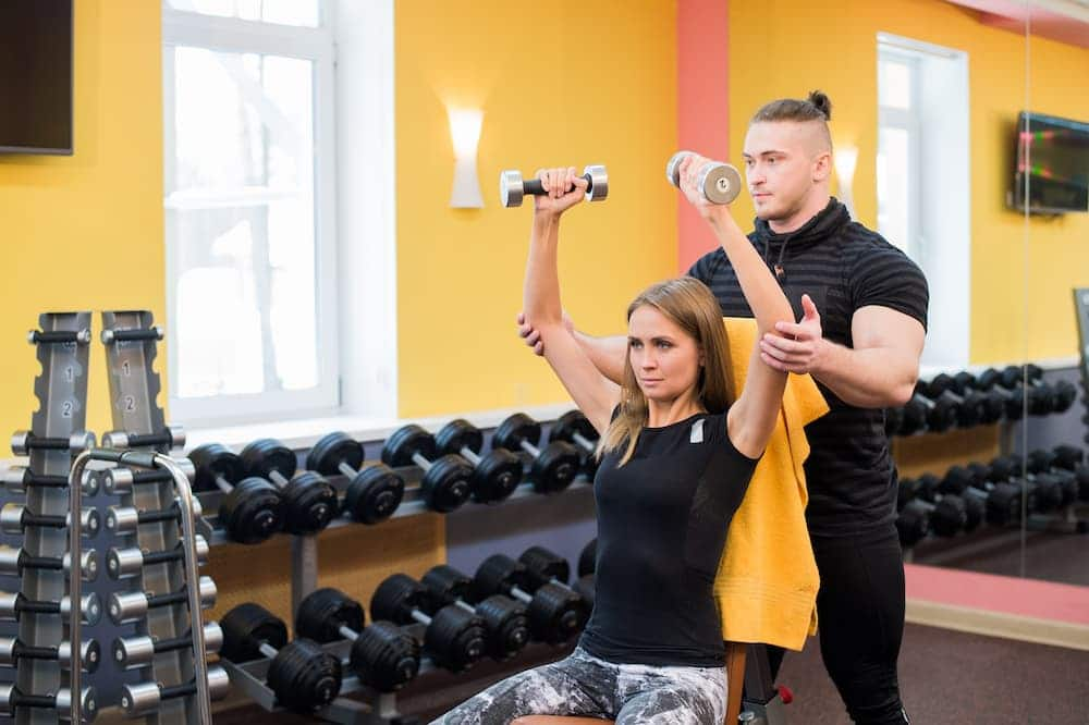 woman with personal trainer at the gym